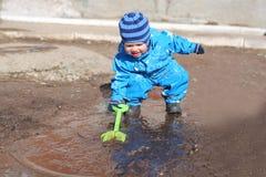 Младенец играя в лужице Стоковая Фотография