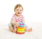 Младенец играя игрушки, башню пирамиды детской игры, образование маленького ребенка