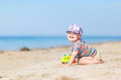 Младенец играя на песчаном пляже стоковое фото
