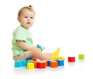 Младенец играя при красочные изолированные блоки стоковое фото