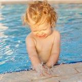 Младенец играя с водой в бассейне стоковое изображение