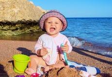 Младенец играя с песком на пляже Стоковая Фотография