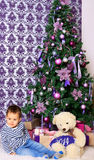 Младенец и плюшевый медвежонок под рождественской елкой Стоковое Изображение