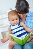 Младенец книги чтения матери Стоковое фото RF