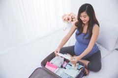 Младенец красивой азиатской беременной женщины организуя одевает на костюме Стоковая Фотография RF
