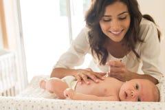 Младенец матери moisturizing Стоковые Изображения RF