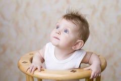 Младенец наблюданный синью на высоком стуле смотря вверх Стоковые Изображения RF