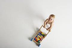 Младенец нажимая тележку с строительными блоками стоковые фотографии rf