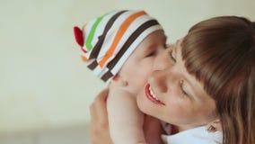 Младенец нежно целует его мать Одетый младенец в striped шортах и крышке видеоматериал