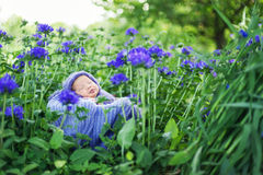 младенец 17 дней старый усмехаясь newborn спит на его животе в корзине на природе в саде внешнем стоковые изображения
