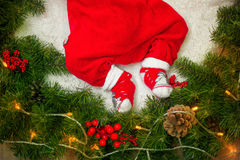 Младенец ног в красном костюме Санте в венке рождества игл сосны с праздничными украшениями Стоковое фото RF