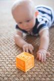 Младенец достигая для блока на сплетенном половике Стоковое Изображение