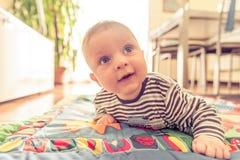 Младенец при голубые глазы играя дома стоковая фотография rf
