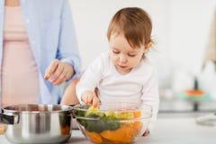 Младенец при овощи и мать варя дома Стоковая Фотография RF