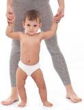 Младенец пробуя сделать первые шаги. Стоковые Изображения