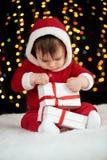 Младенец распаковывает подарочные коробки при украшение рождества, одетое как Санта, света boke на темной предпосылке, концепции  Стоковые Изображения
