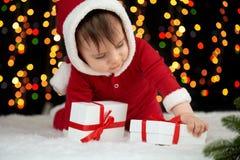 Младенец распаковывает подарочные коробки при украшение рождества, одетое как Санта, света boke на темной предпосылке, концепции  Стоковое Изображение
