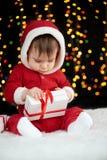 Младенец распаковывает подарочные коробки при украшение рождества, одетое как Санта, света boke на темной предпосылке, концепции  Стоковые Фотографии RF