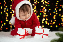 Младенец распаковывает подарочные коробки при украшение рождества, одетое как Санта, света boke на темной предпосылке, концепции  Стоковая Фотография RF