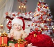 Младенец рождества в шляпе Санты, подарке настоящего момента Xmas детей стоковые изображения rf