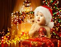 Младенец рождества раскрывая присутствующую, счастливую шляпу Санты ребенк, подарок Xmas стоковые фотографии rf