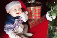 Младенец рождества сидя около рождественской елки и подарочной коробки! Стоковые Фотографии RF