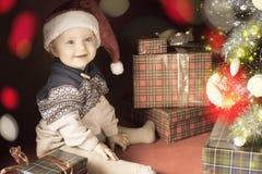 Младенец рождества сидя около рождественской елки и подарочной коробки! Стоковое Изображение RF