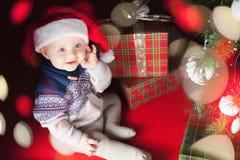 Младенец рождества сидя около рождественской елки и подарочной коробки! Стоковая Фотография RF
