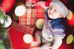 Младенец рождества сидя около рождественской елки и подарочной коробки! Стоковое Изображение