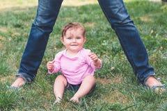 Младенец сидя на траве Стоковая Фотография