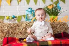 Младенец сидя около украшений пасхи Стоковое Изображение
