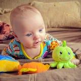 младенец смотря игрушки Стоковая Фотография