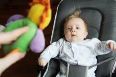 Младенец смотря игрушку Стоковые Изображения