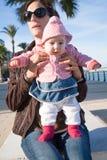 Младенец стоя на ногах матери в улице стоковое изображение