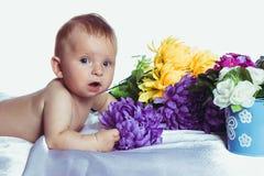 Младенец с голубыми глазами лежит в цветах стоковое изображение rf