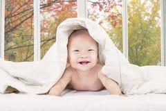 Младенец усмехаясь на камере на спальне Стоковая Фотография