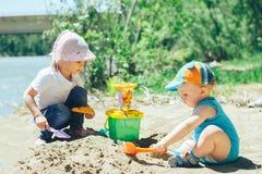 2 младенца играя на пляже с песком Стоковое Фото