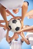 Младшая футбольная команда держа шарик Стоковые Изображения RF
