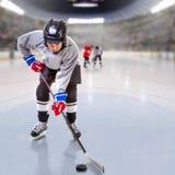 Младшая шайба хоккеиста регулируя в арене Стоковые Изображения RF
