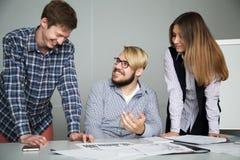 Младший главный бухгалтер смеется над на этой задаче и говорится о ем к коллегам Стоковая Фотография