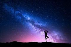Млечный путь с силуэтом йоги стоящей женщины практикуя Стоковые Фото