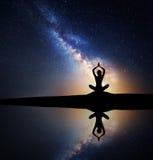 Млечный путь с силуэтом сидя йоги женщины практикуя Стоковое Изображение RF