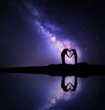 Млечный путь Человек и женщина держа руки в форме сердца Стоковое Изображение