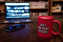 Наблюдая серия с чашкой чаю на деревянной таблице с мобильным телефоном Как раз один больше эпизода Тысячелетнее conceptn стоковое фото rf