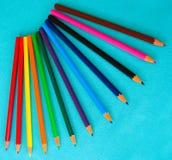 Набор детей, покрашенных карандашей на предпосылке бирюзы стоковая фотография