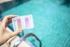 Набор испытания испытания воды бассейна в руке девушки над запачканной ясной голубой водой бассейна стоковое изображение rf