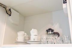 Набор и чайник чая на полке в кухонном шкафе кухни стоковая фотография rf