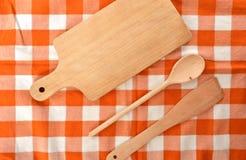 Набор кухни сделанный от древесины на checkered оранжевом белом dishtowel Стоковое Изображение RF