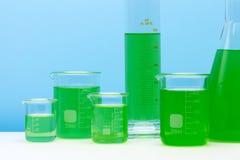 Набор лаборатории стеклянный заполненный с зеленым веществом стоковое изображение