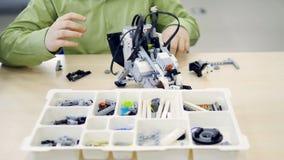 Набор молодого школьника собирая модельный футуристического робота 4K сток-видео
